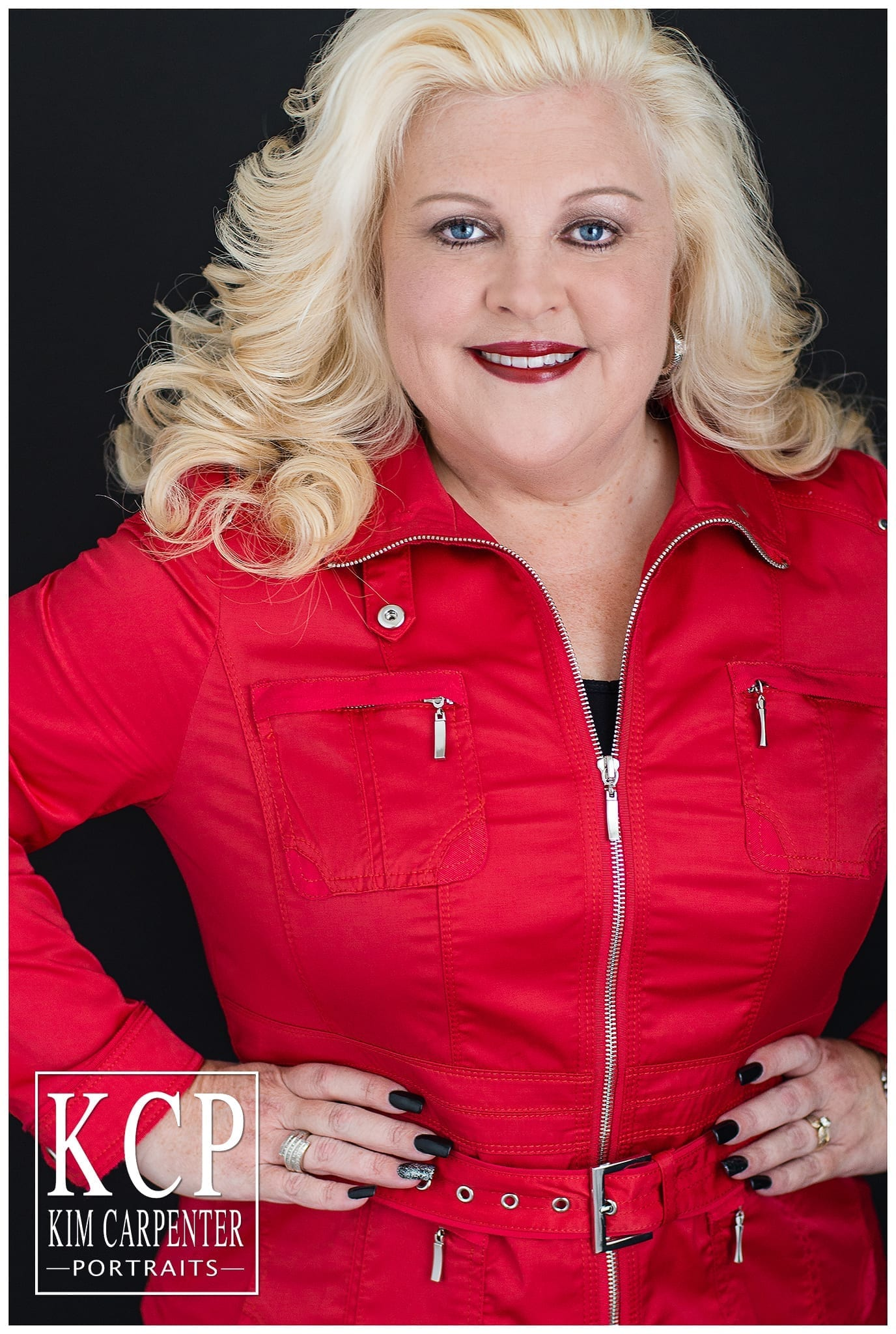 A close photograph of a woman wearing a bright red jacket with her hands on her hips. Lakeland Photographer, professional headshots
