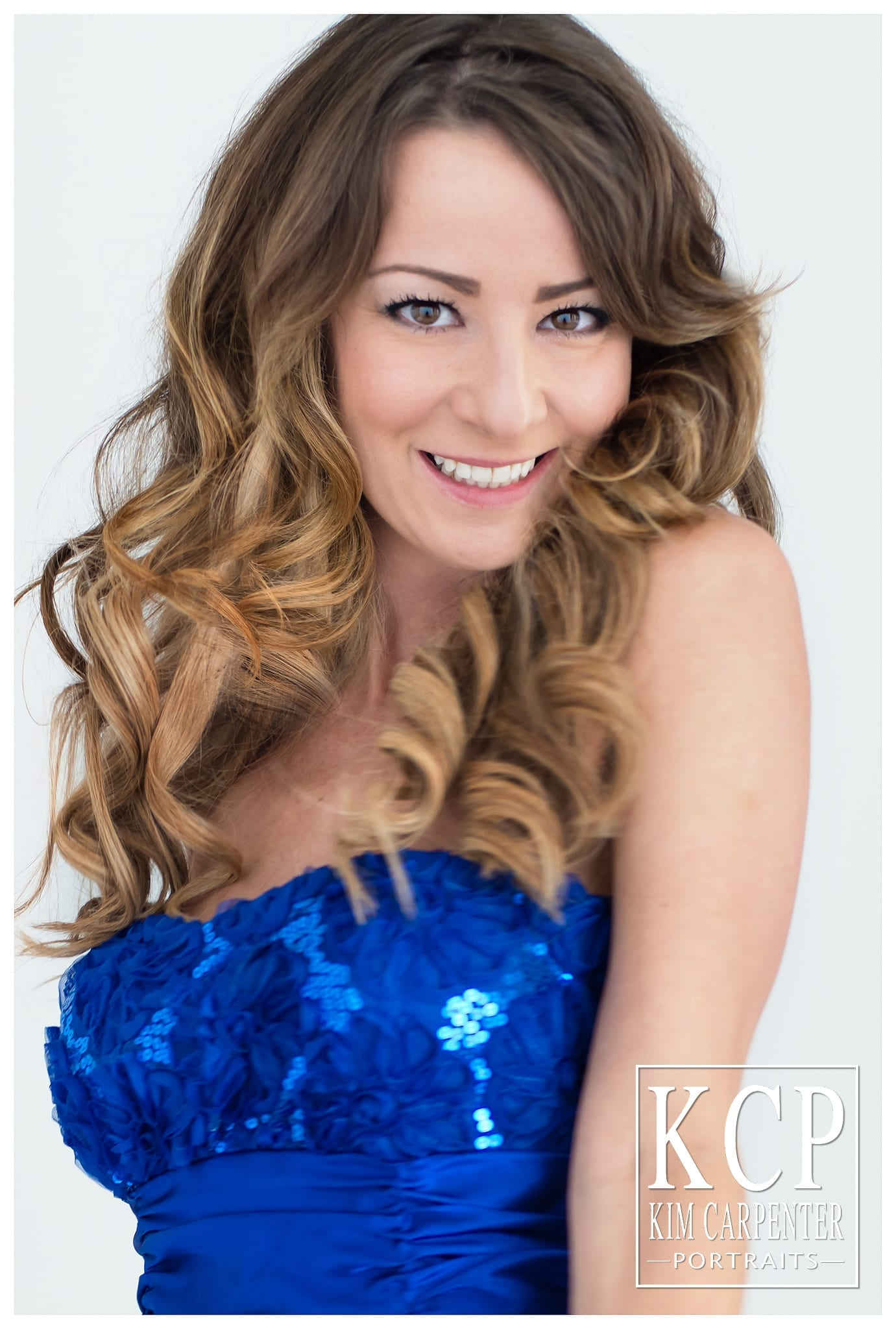 Woman with curly brown hair looking into the camera lens with brown eyes. Lakeland Photographer, professional headshots