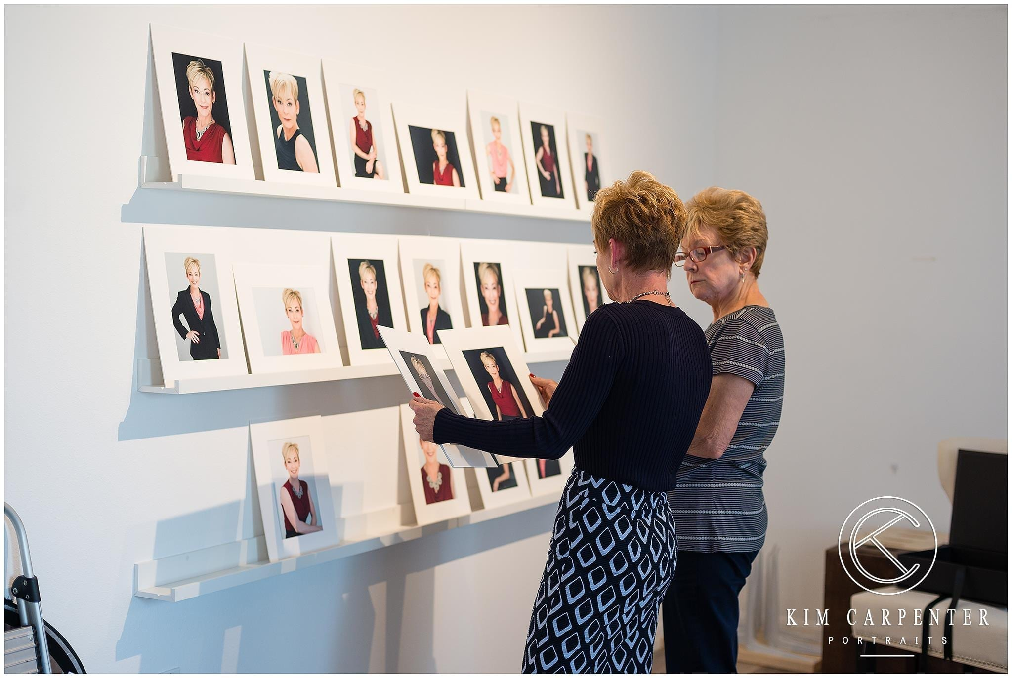 two women, mom and daughter, looking at professional portraits of the daughter