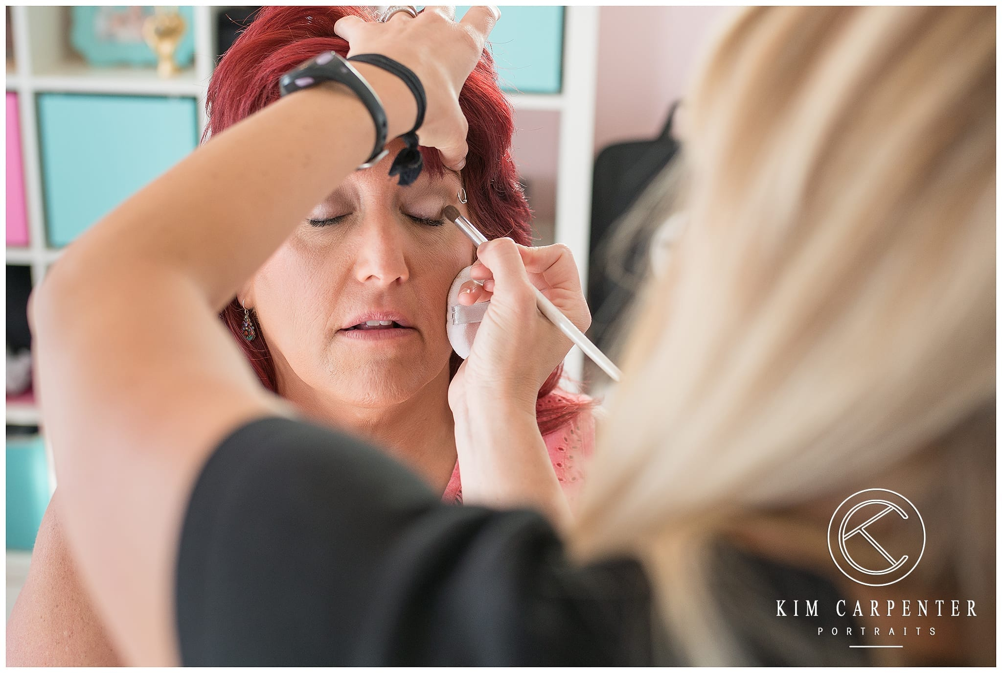 Woman getting makeup applied to her eyes.