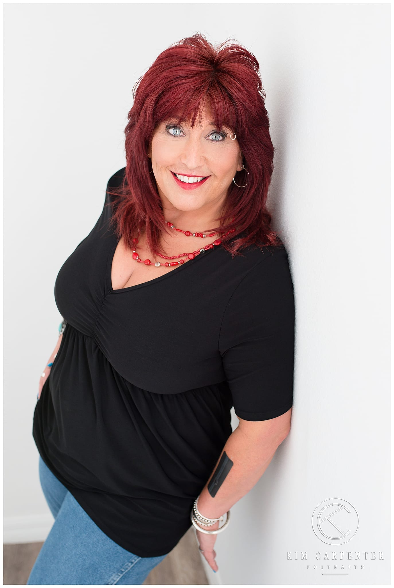 Woman leaning against a wall and facing the photographer. Lakeland Photographer, professional headshots