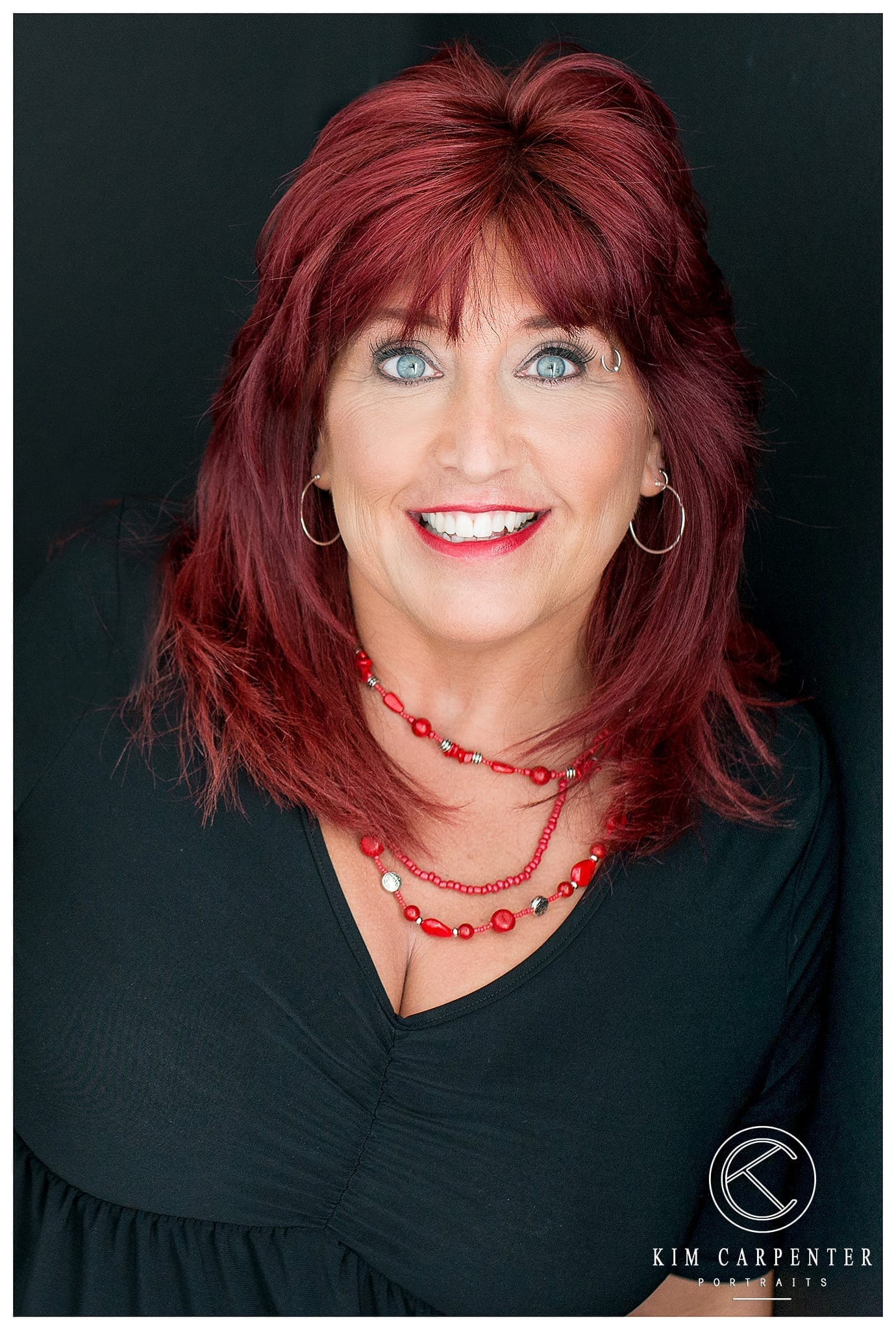 Woman smiling at camera with a black shirt and red necklace. Lakeland Photographer, professional headshots