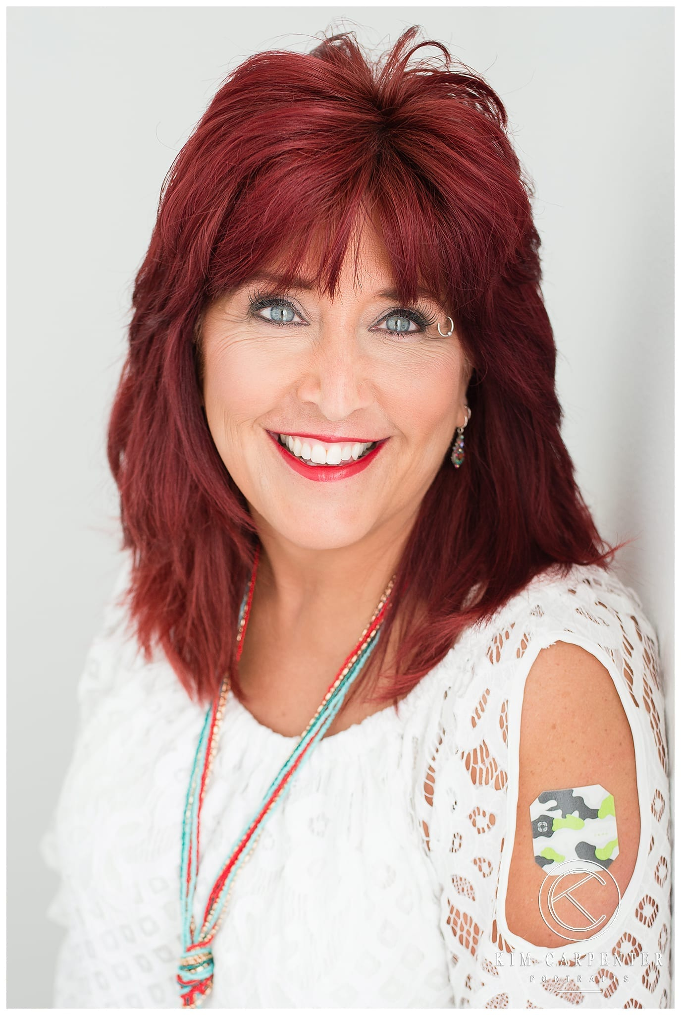 Woman wearing a white lace shirt and a Thrive sticker is showing on her shoulder. Lakeland Photographer, professional headshots