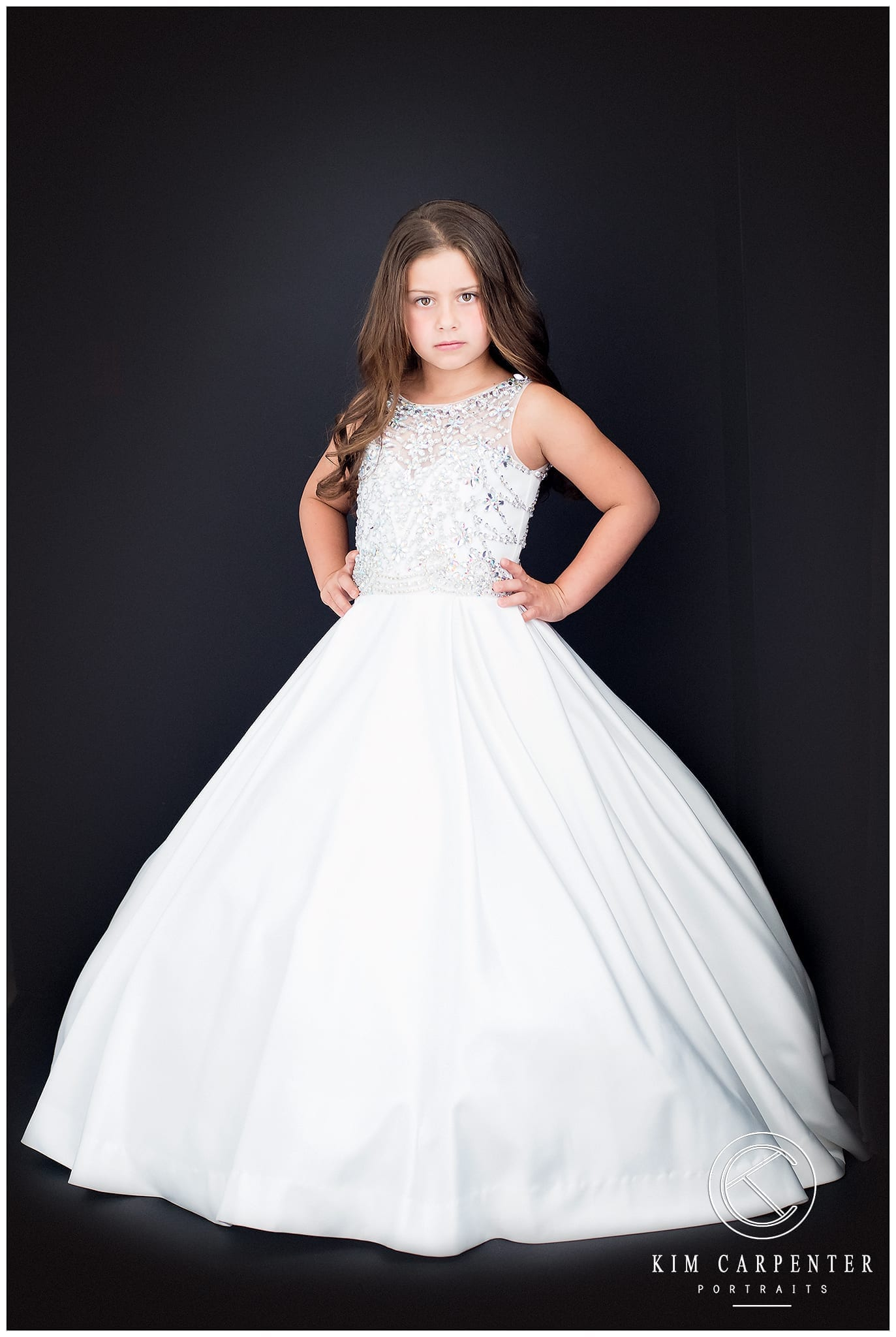 beautiful little girl in a long white gown with a black background