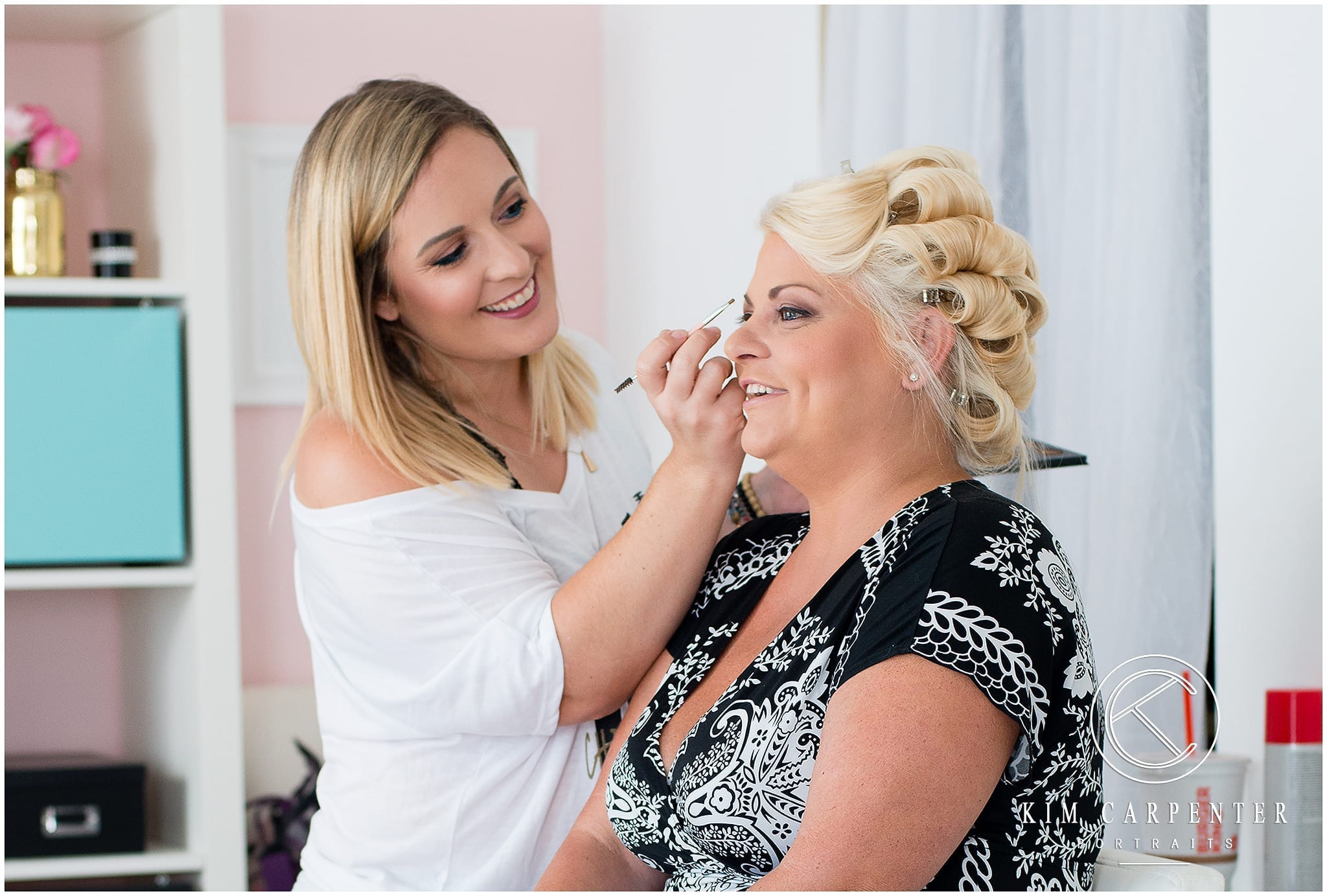 Woman with her hair in curlers getting her makeup done.