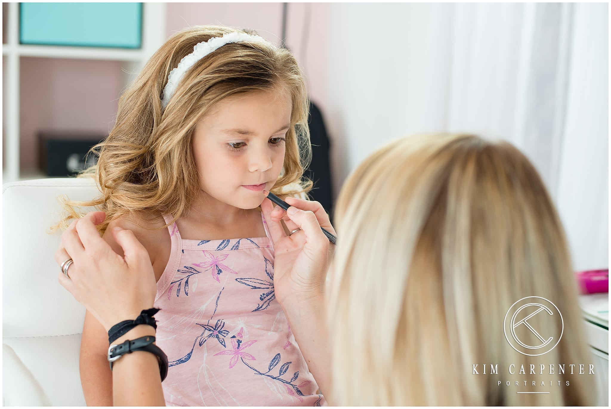 Picture of woman doing little girl's makeup