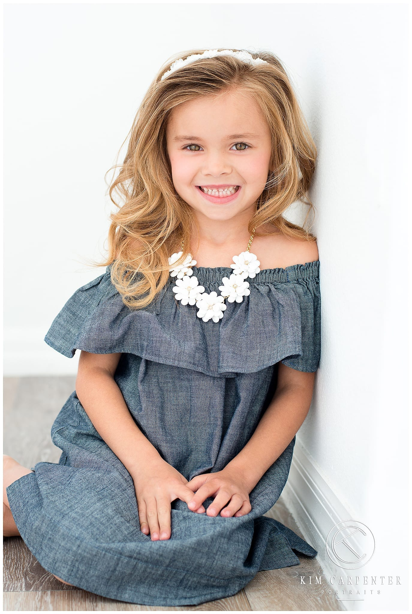 Little girl wearing a white flower necklace.