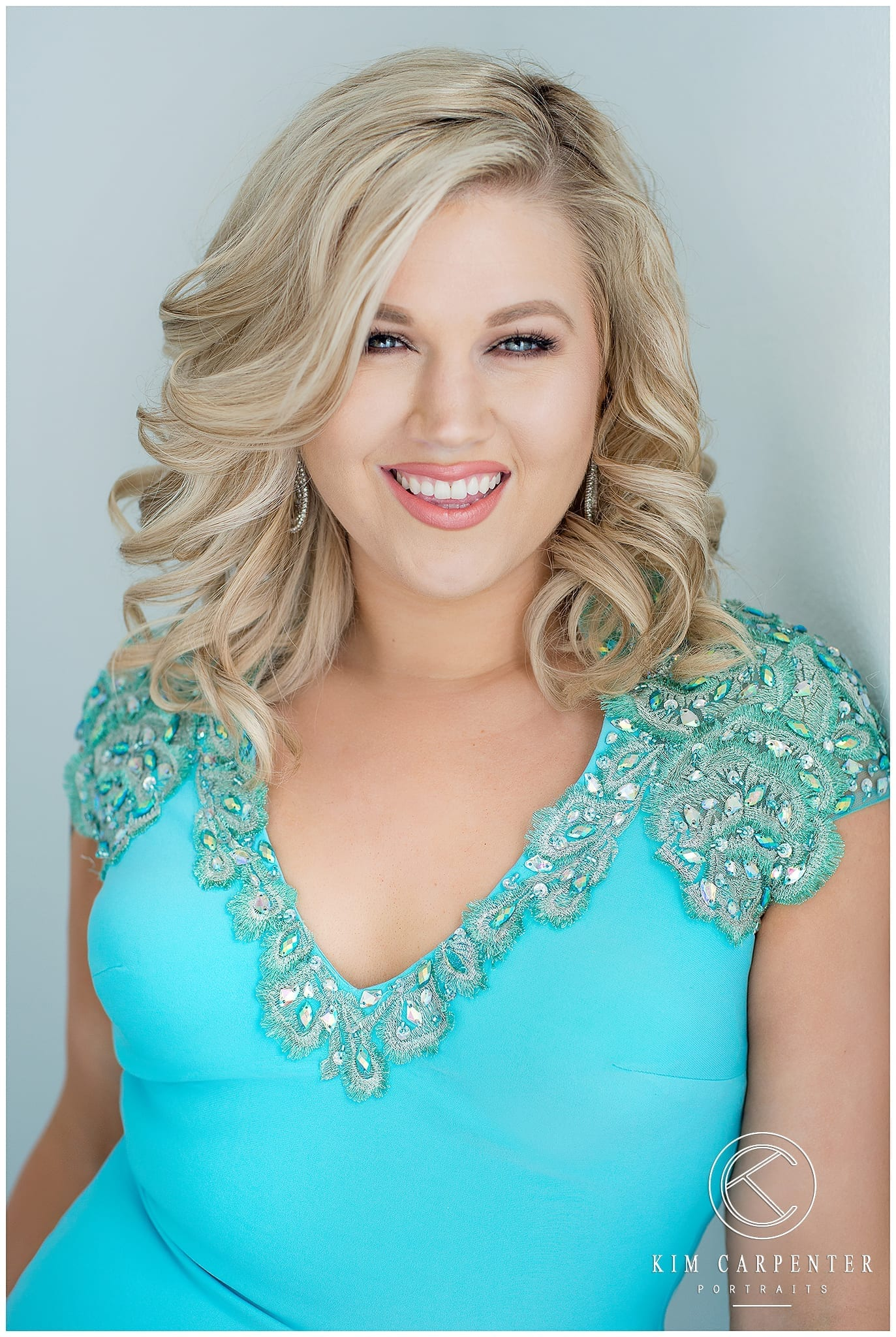 Woman smiling and posing for camera with blonde curls and a blue dress. Lakeland Photographer, professional headshots