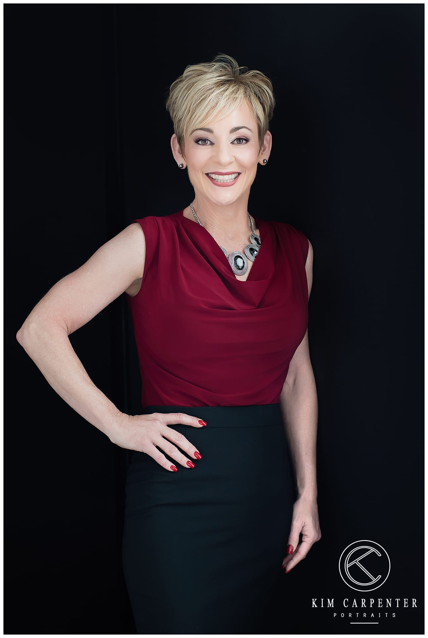 Woman wearing maroon shirt and black shirt, posing for camera with her hand on her hip. Lakeland Photographer, professional headshots
