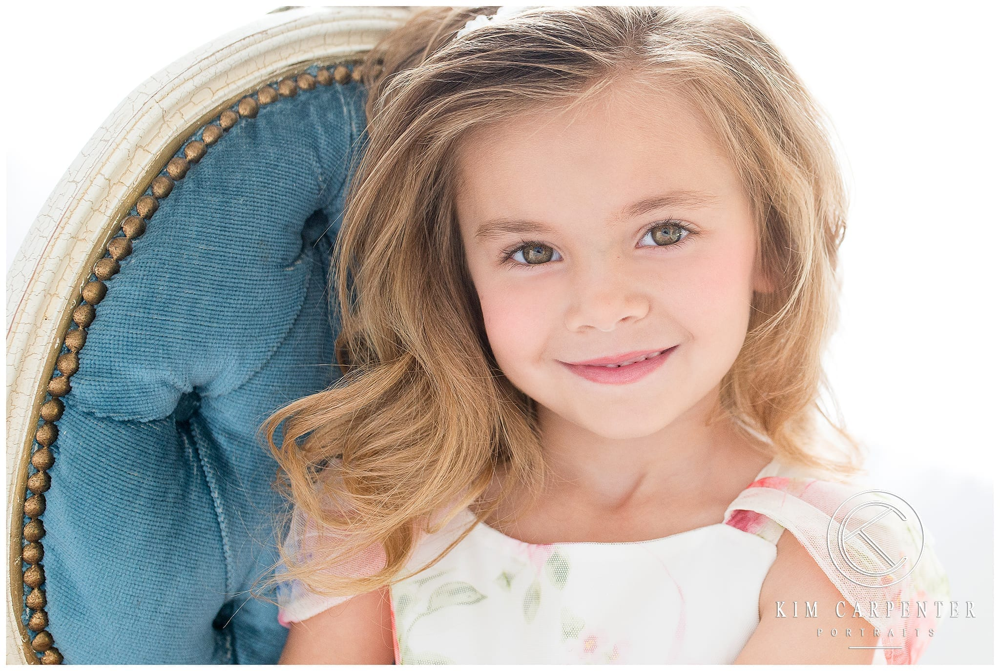 A close up of a little girl smiling with a chair in the background.