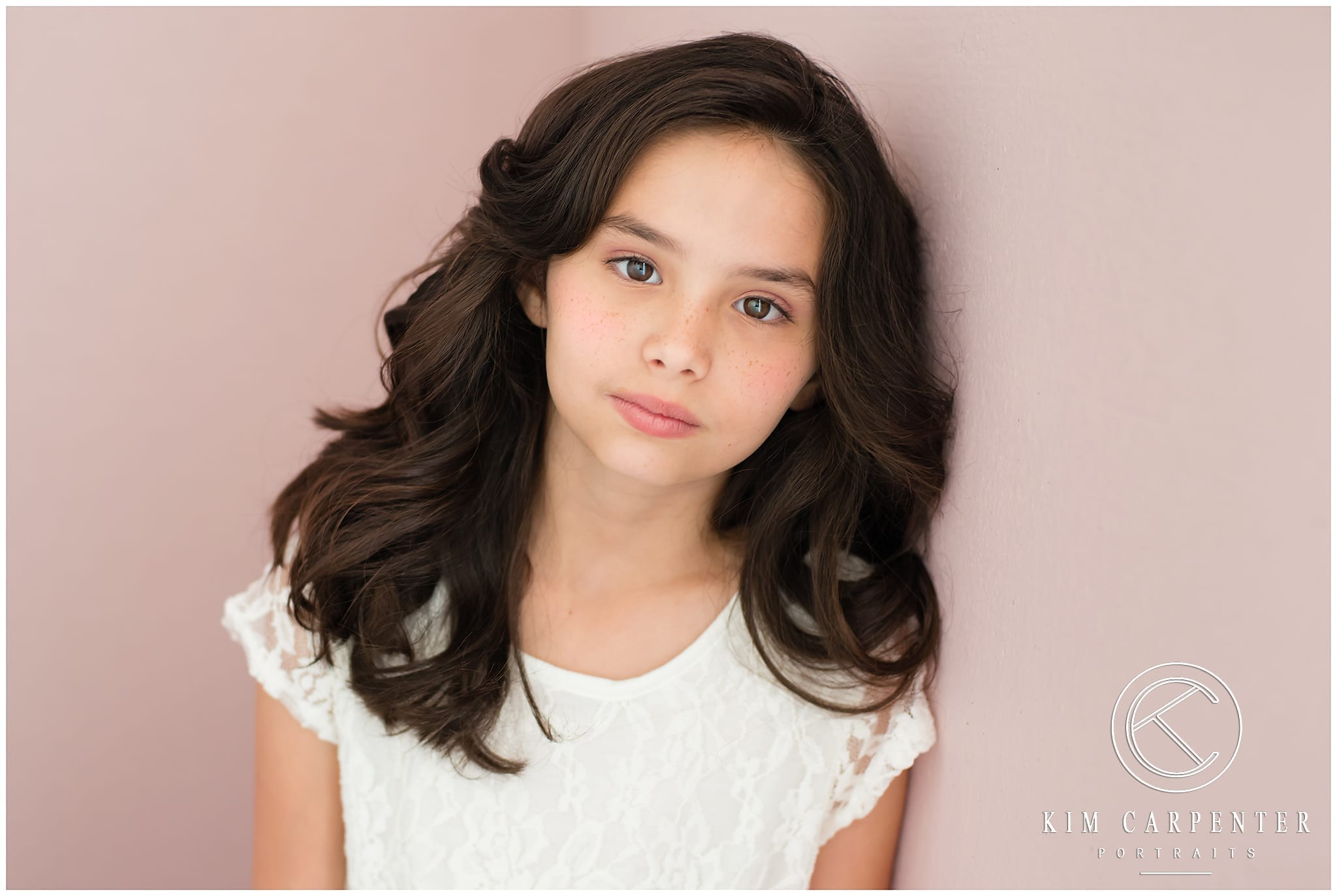 Girl leaning against a pink wall looking at camera.
