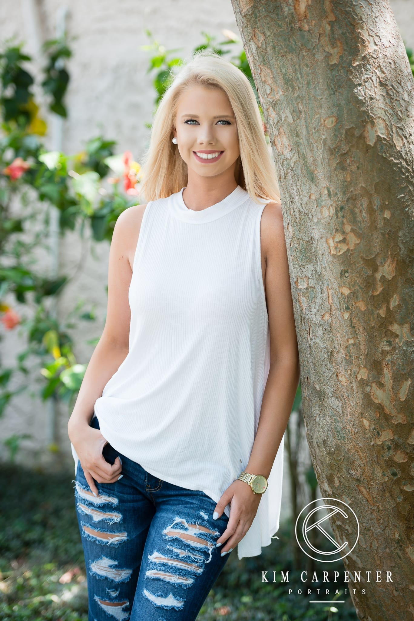 Senior wearing white tank top and ripped jeans.