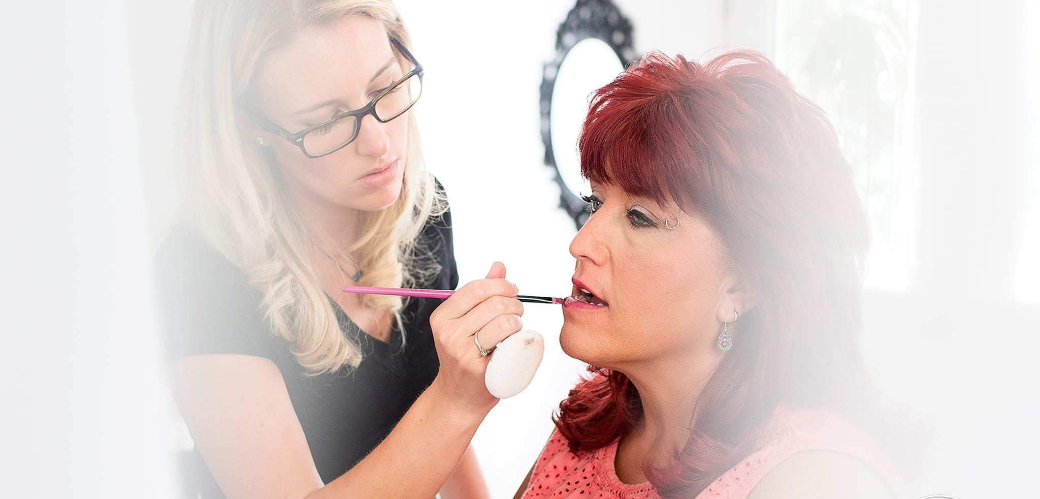 Woman applying lipstick to another woman's lips for a professional headshots session.
