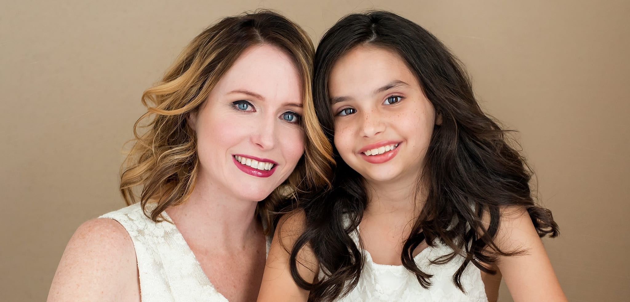 Woman and daughter smiling for their mommy and me shoot.
