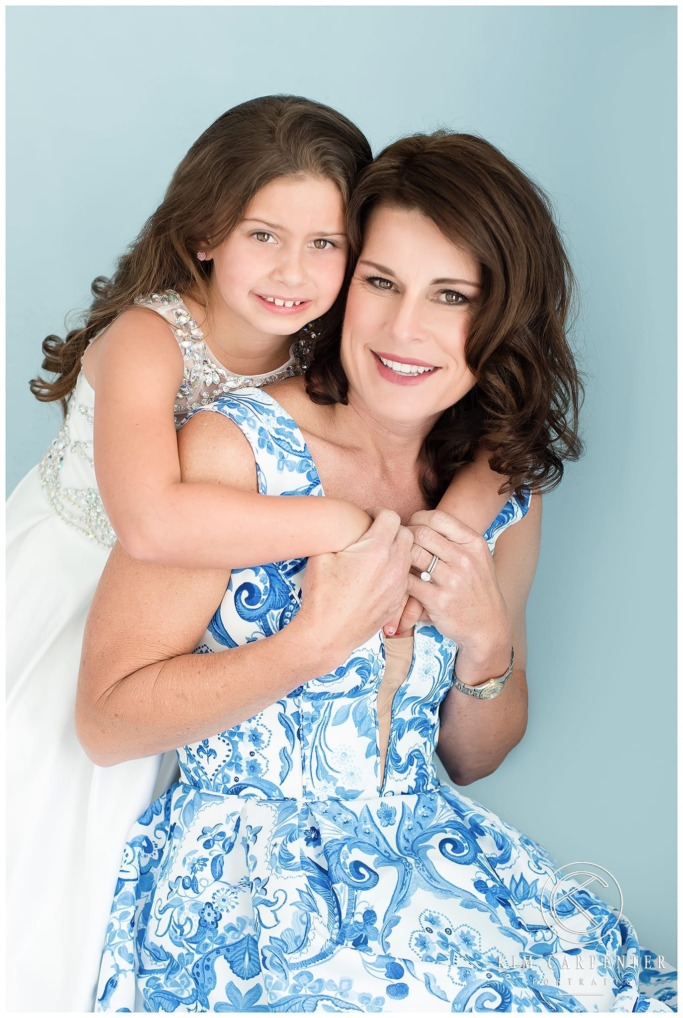 Lakeland Photographer - Mother and daughter hugging each other in blue and white dresses with a blue background