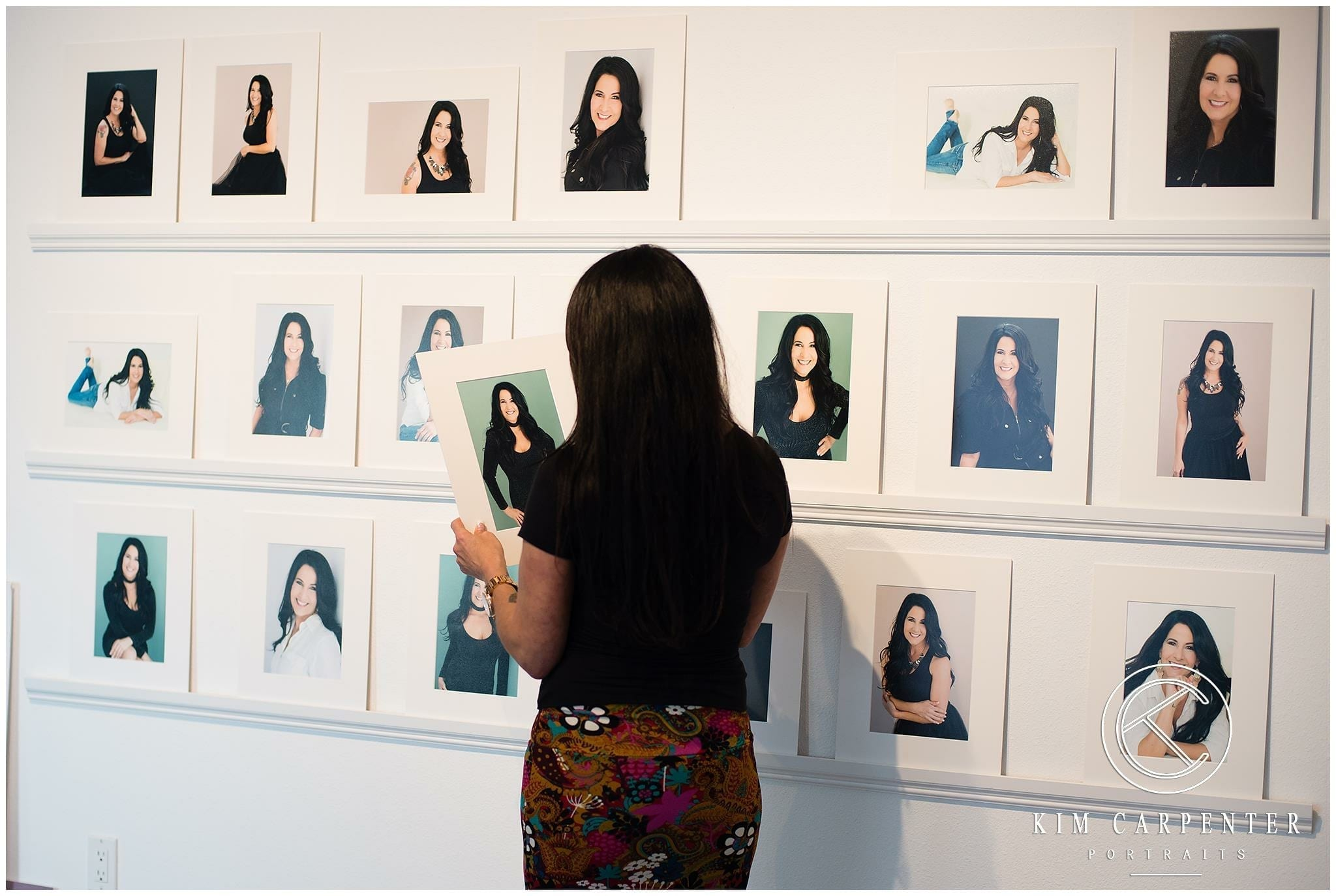 A woman standing and looking at personal headshots on shelves.
