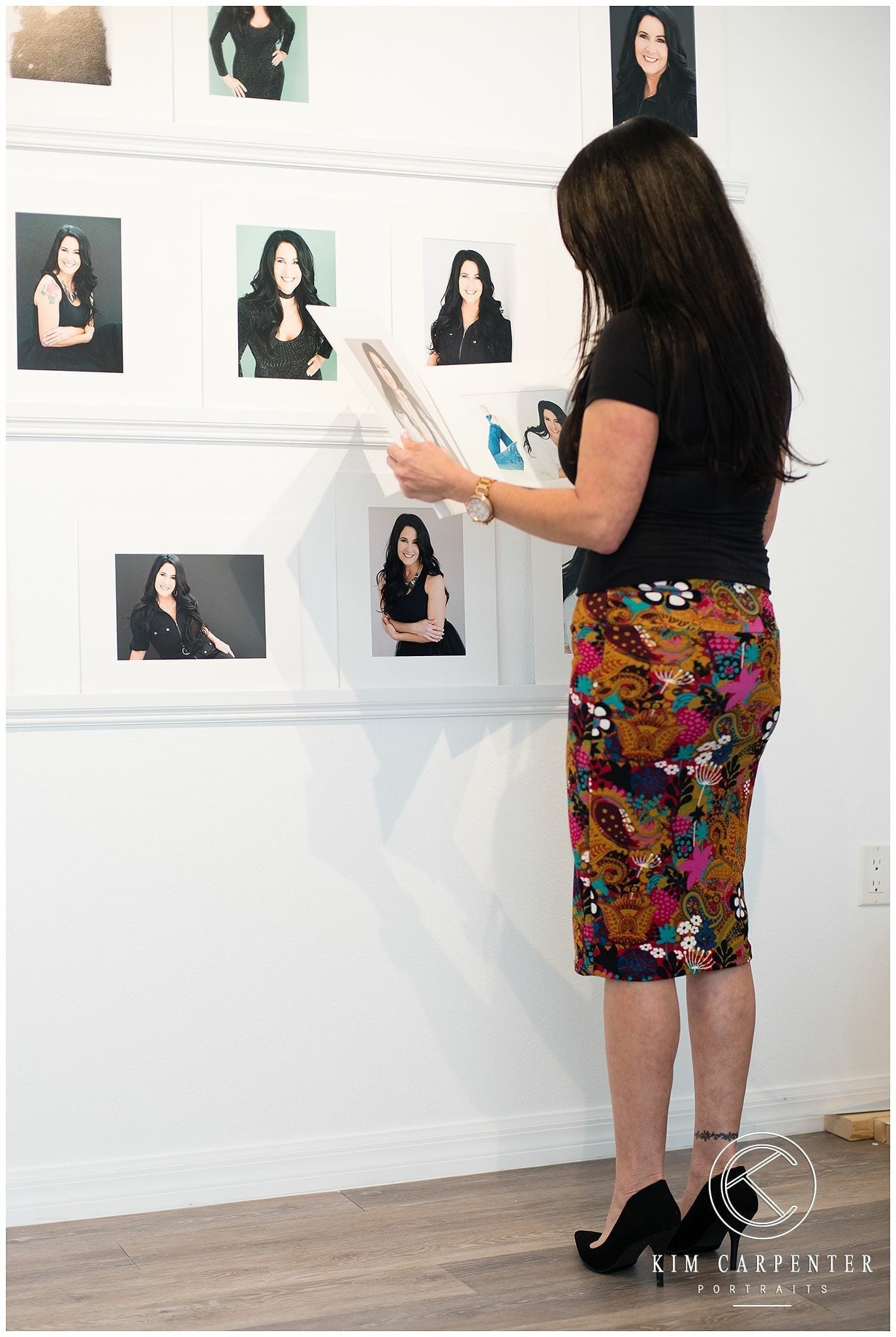Woman looking at professional headshots on a wall.