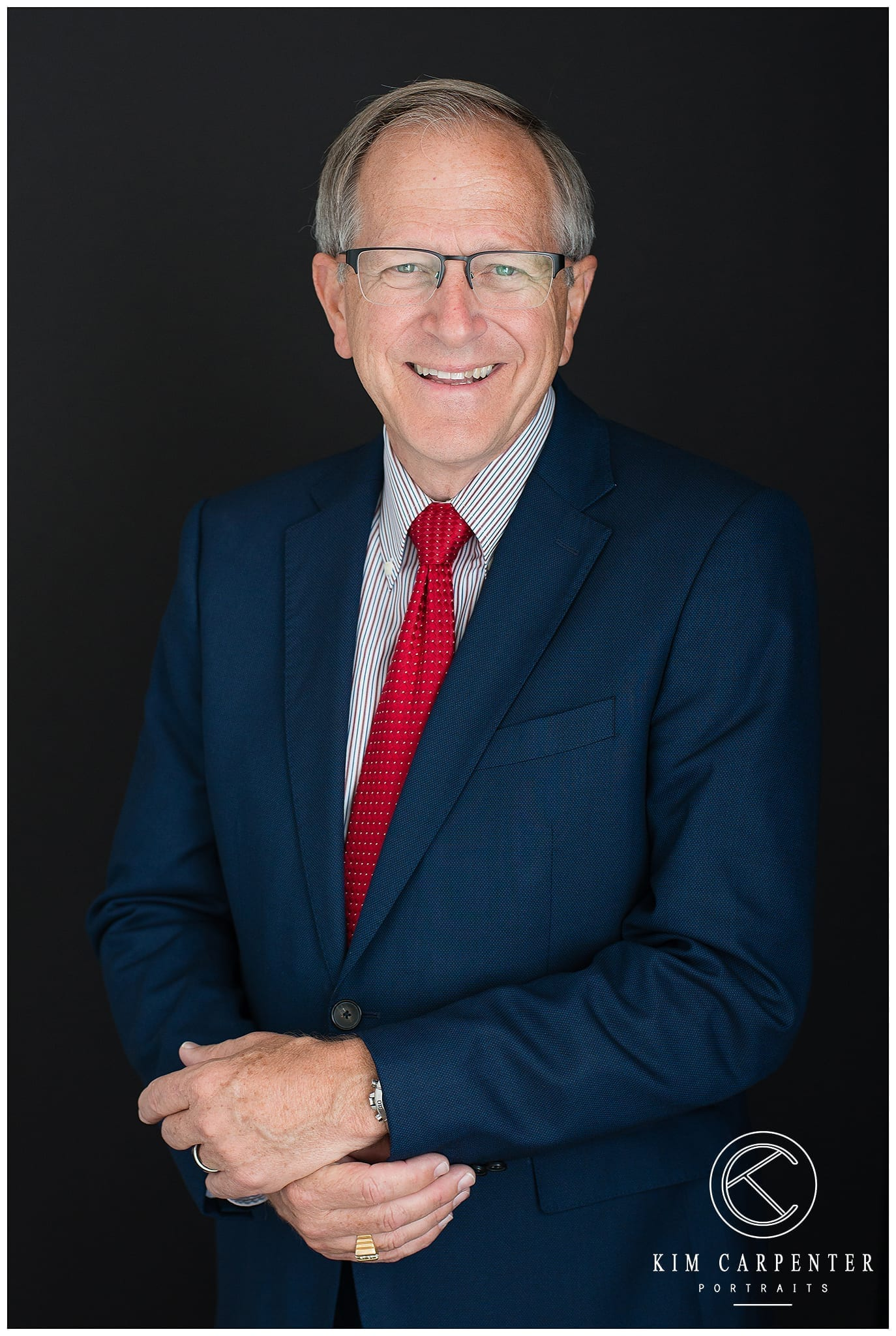 Bill Mutz is wearing a red tie and smiling for his professional headshots. Lakeland Photographer, professional headshots