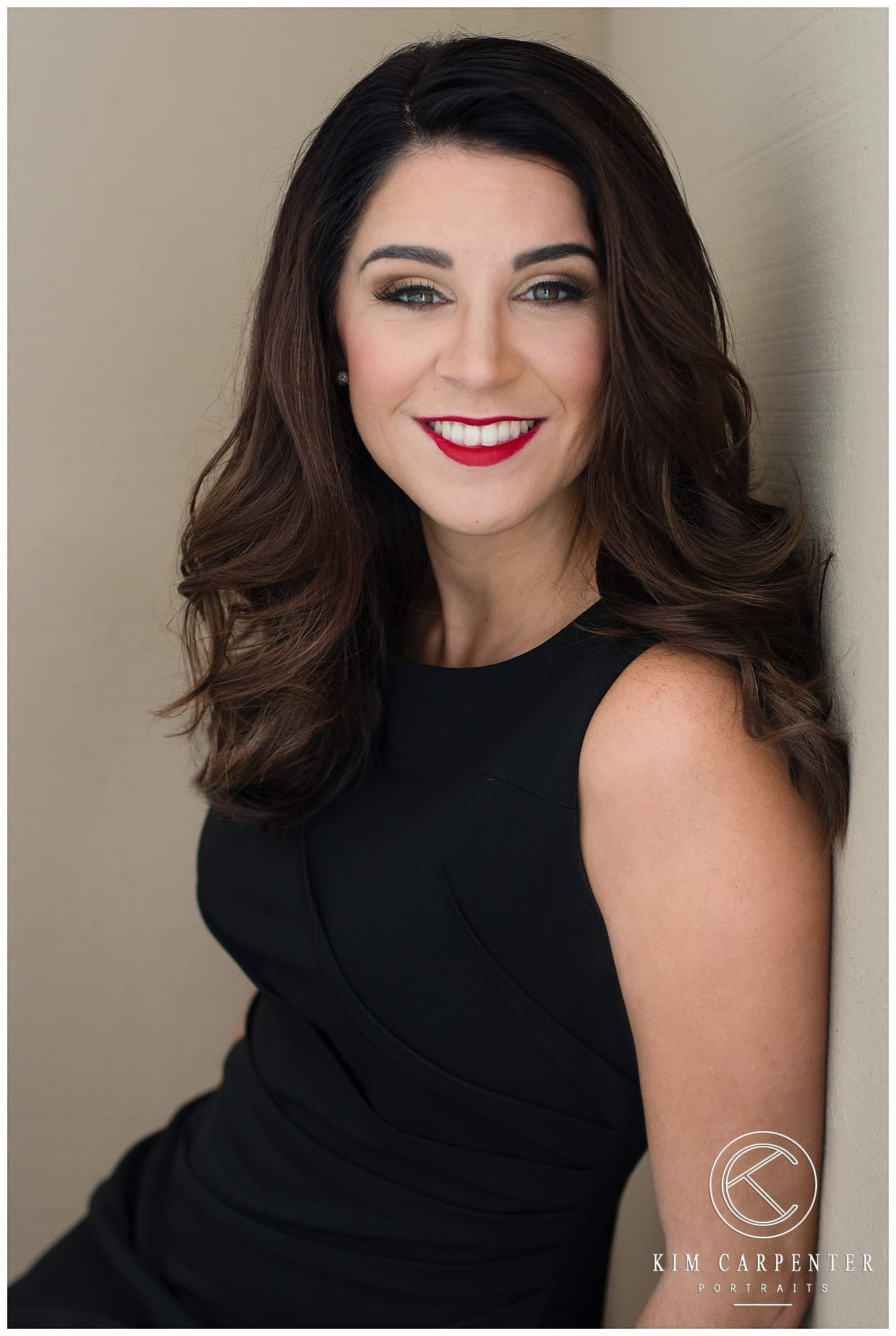 Girl leaning against a tan wall wearing a black dress. Lakeland Photographer, professional headshots