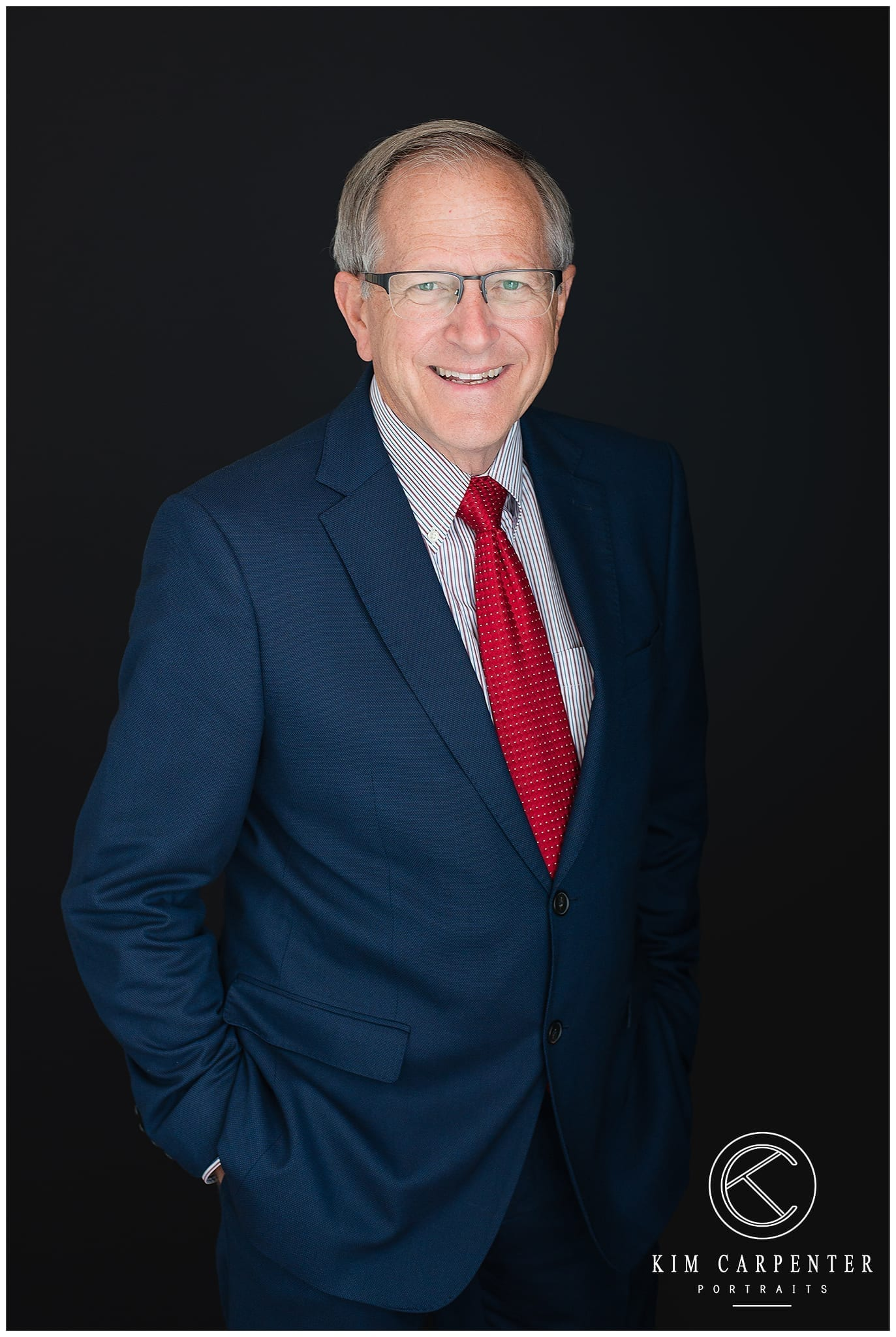 Man standing with a black background and wearing glasses. Lakeland Photographer, professional headshots