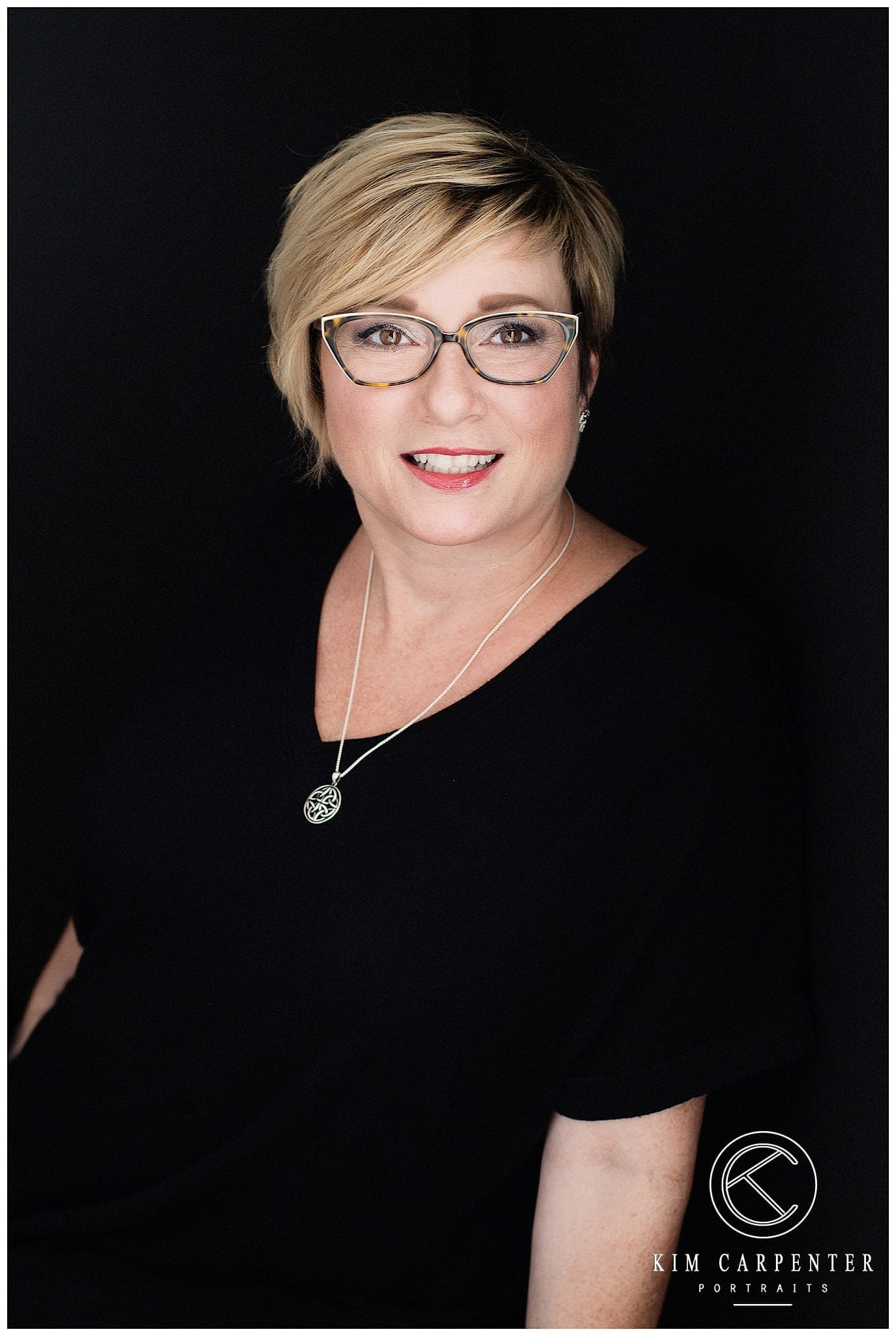 Lady with short hair and glasses with a beautiful necklace on.