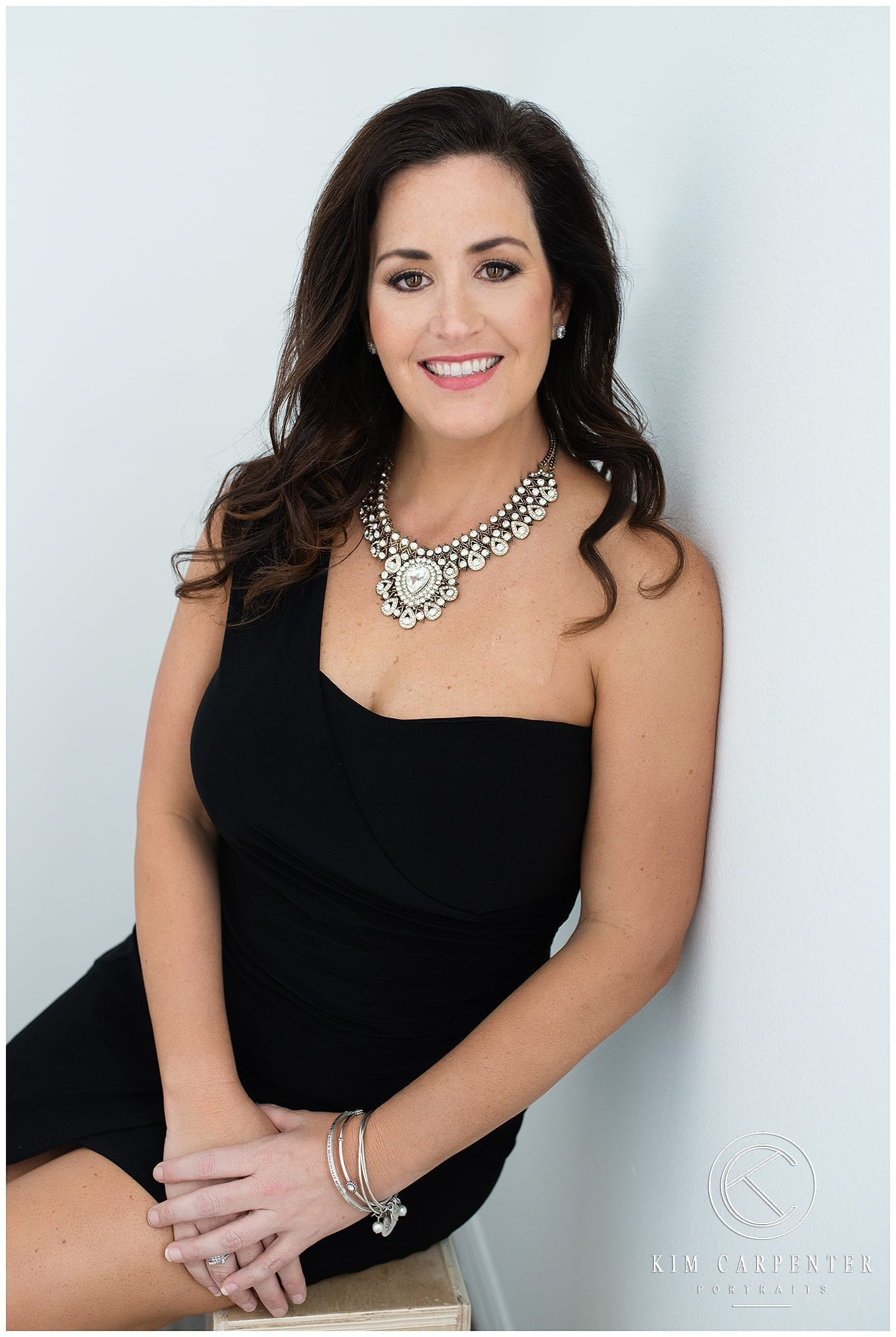 Beautiful woman wearing a black dress and a blingy necklace smiling at a camera.