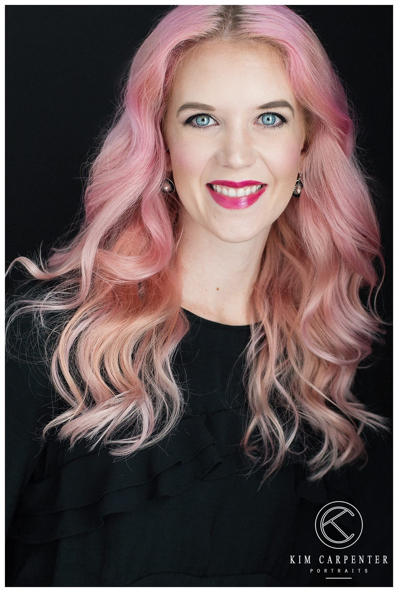 A woman with pastel pink hair and bright red lips.