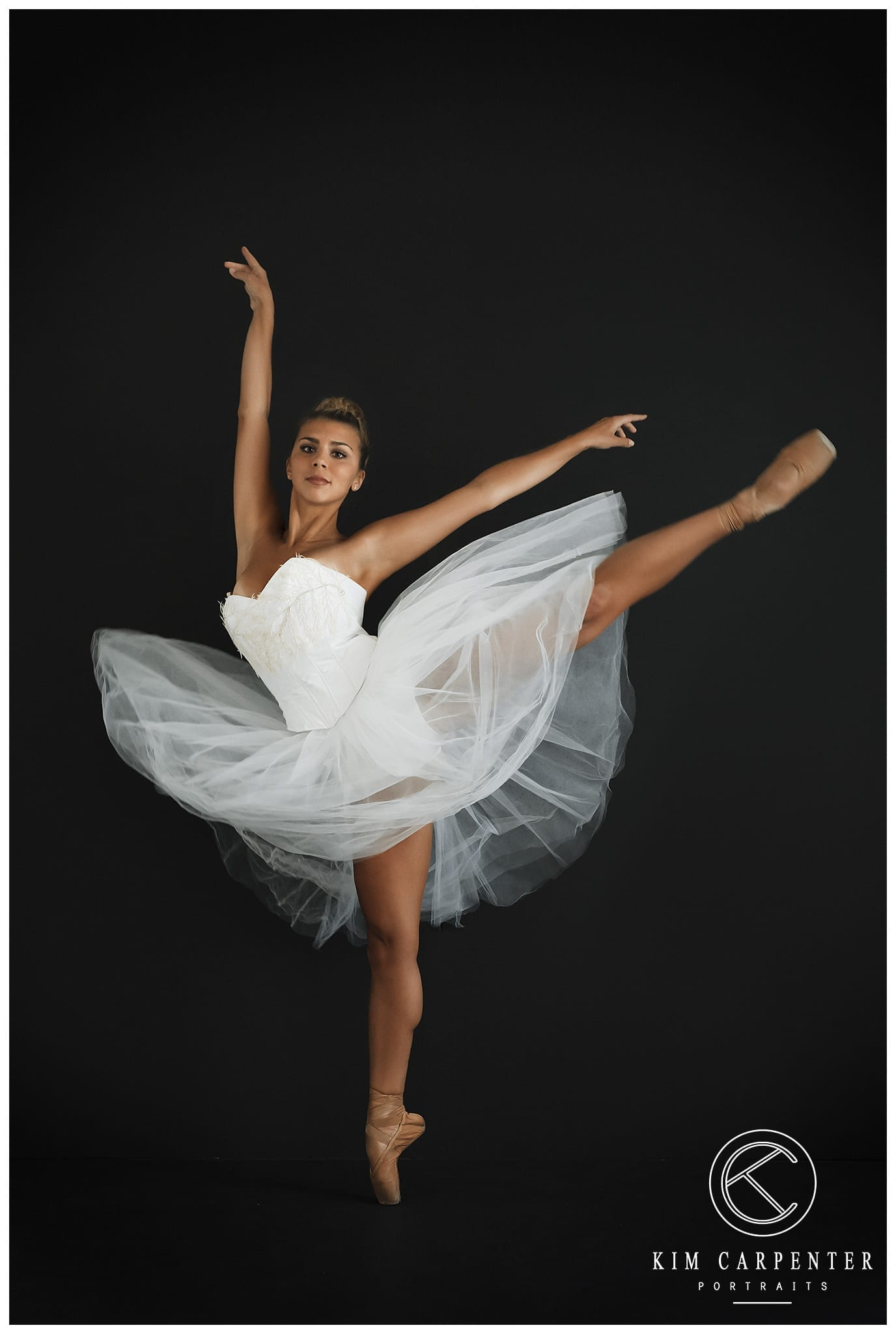A black background with a dancer dressed in white with one leg high.