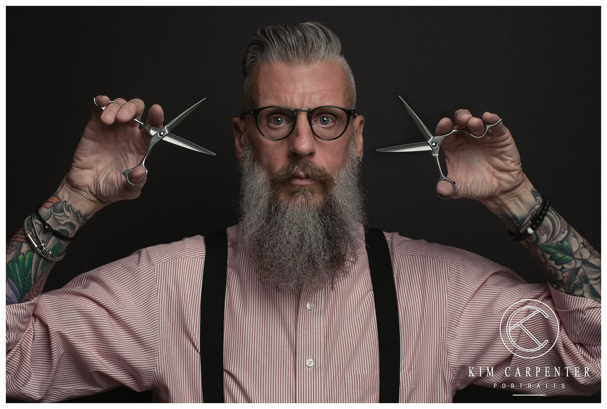 Man holding two pairs of hair cutting scissors.