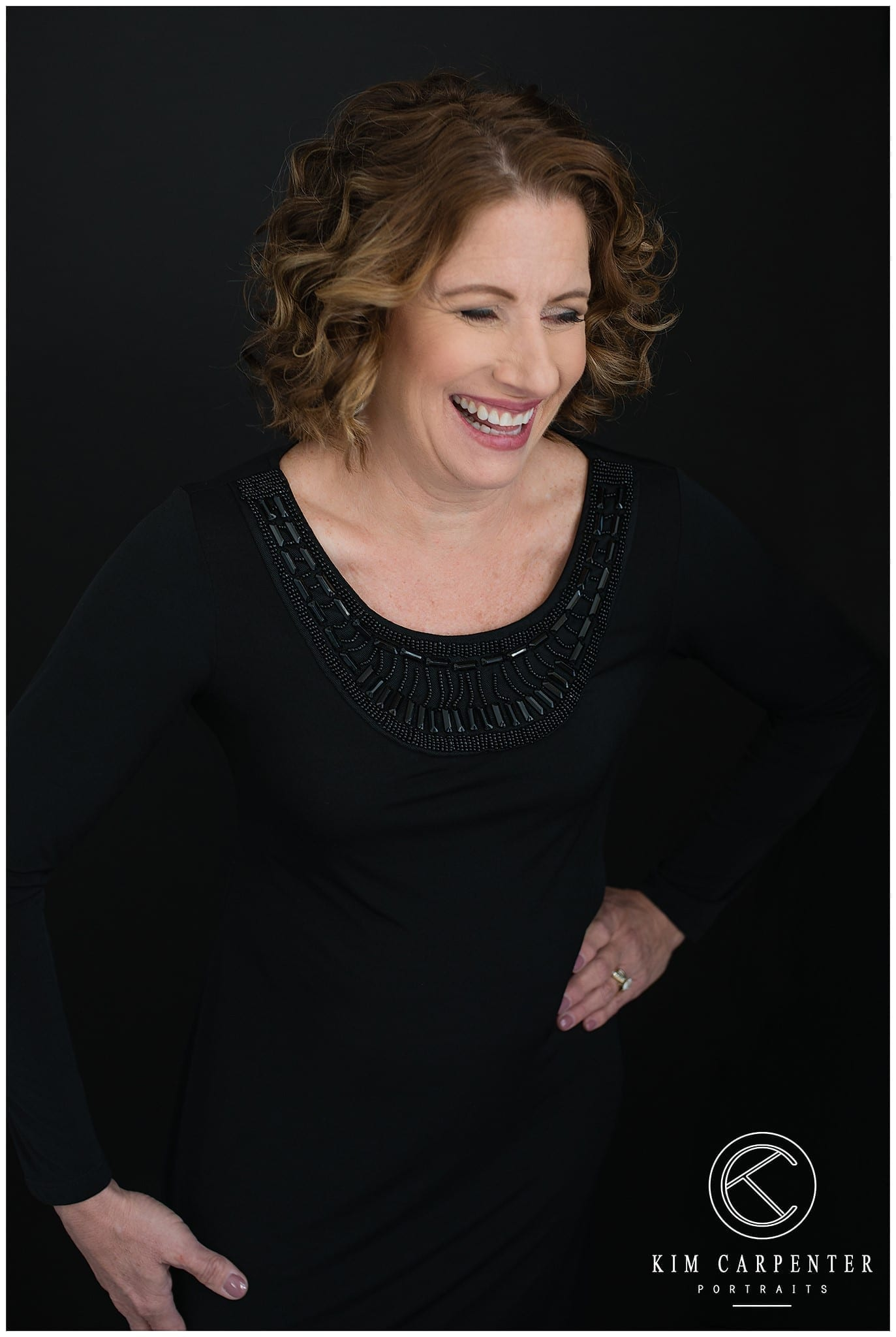 Image captured of a woman laughing wearing black.